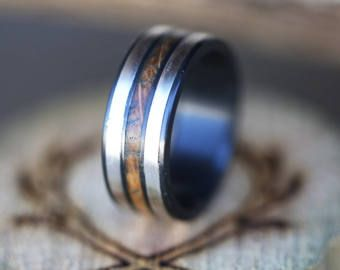 Each of our rings is a handcrafted one-of-a-kind piece, and is made to order for you and your significant other by a passionate and skilled artisan.This ring is features in titanium with a whiskey barrel overlay. Different inlay options available upon request.  Available in: TITANIUM, SILVER, BLACK ZIRCONIUM, 10K WHITE, YELLOW, OR ROSE GOLD  When ordering in gold PLEASE remember to select white, yellow or rose gold in the notes from the buyer section during checkout. If no color is selected…