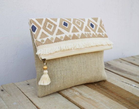 Bohemian natural colour embroidered foldover clutch. The multipurpose pouch or purse is very trendy,handy, rustic and light inspired by Moroccan handira blanket designs. The clutch is embroidered and ornamented with cotton fringe and dull gold sequins  It is made of natural colour linen and cream colour cotton duck fabric The inside is lined with matching natural cotton fabric The bag has matching zip closure with brass puller which is decorated with funky, bohemian hand made tassel  Size…