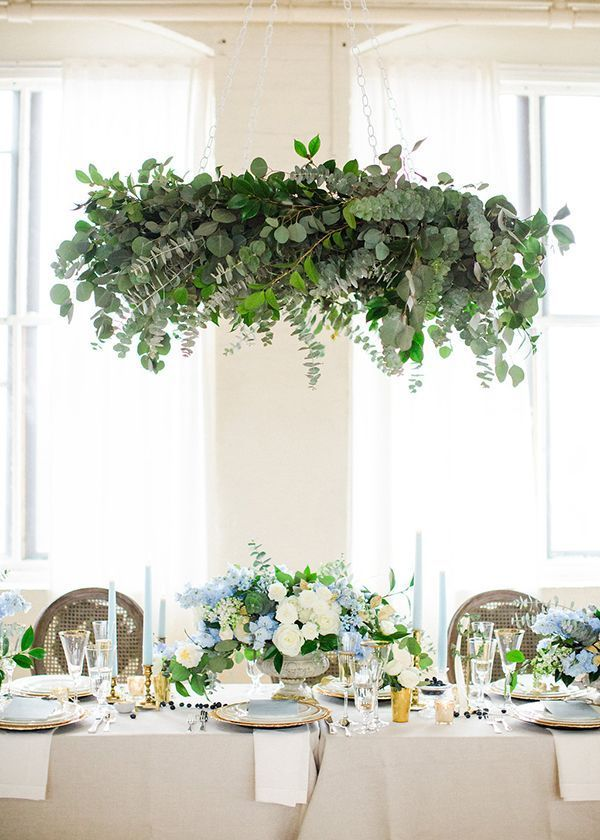 Dramatically draped with eucalyptus and camellia foliage, a leafy chandelier was the indisputable showpiece of the shoot. Suspended above the tabletop, it complemented rather than overwhelmed the centerpiece beneath it.   Photo by Deborah Zoe