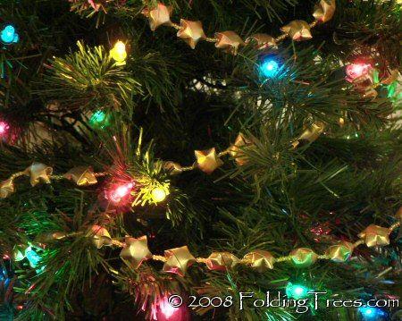origami star Christmas tree garland. Use seasonal paper & this tutorial to make this adorable garland:  http://foldingtrees.com/2008/06/lucky-wishing-stars-tutorial/