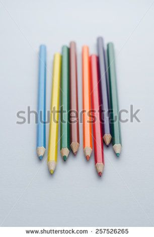 Closeup of wooden colored crayons over blue background, shallow depth of field
