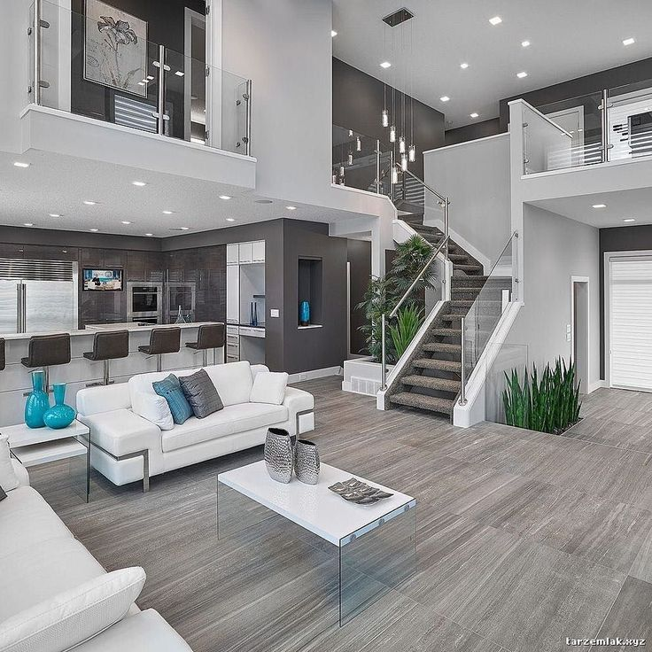 OPEN-FLOOR PLAN is the way to go!  Open concept living room & kitchen with gray walls hardwood floors & flawlessly placed blue and green accents  to bring a splash of color.  #openconcept #hardwoodfloors #grayandwhite Photo by Prorail Systems LTD.