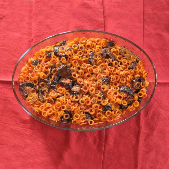 Ingredienti: 300 gr anelli siciliani 400 gr passata pomodoro 1/2 dado vegetale 3 spicchi d'aglio peperoncino in polvere 4 piccole melanzane lunghe 1 cucchiaio di olive nere denocciolate 150 gr di p...