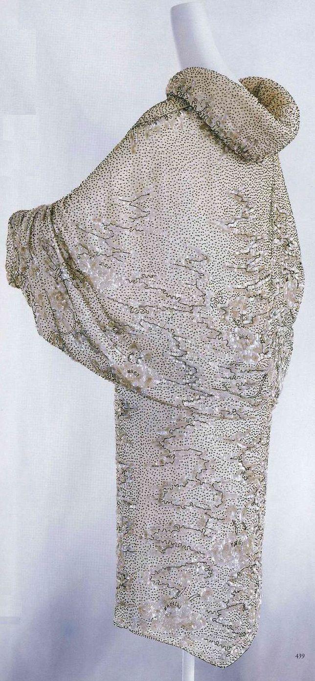 Вечернее манто. Около 1925, Франция. Белая хлопчатобумажная вуаль, вышивка черным и серебряным бисером и пайетками, узор в виде лотосов и волн, воротник с подбивкой, складку на середине спинки поддерживает другая ткань изнутри.