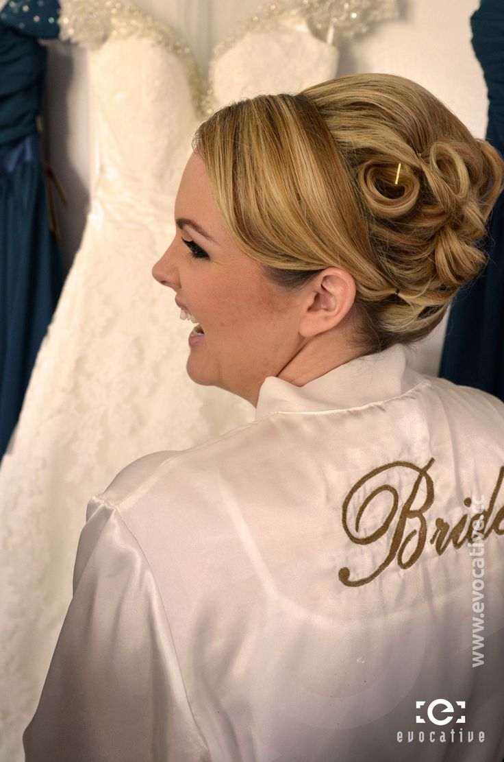 The bride in her custom embroided dressing gown, enjoying seeing her wedding dress and the bridesmaid dresses hanging up together. #WeddingPhotography