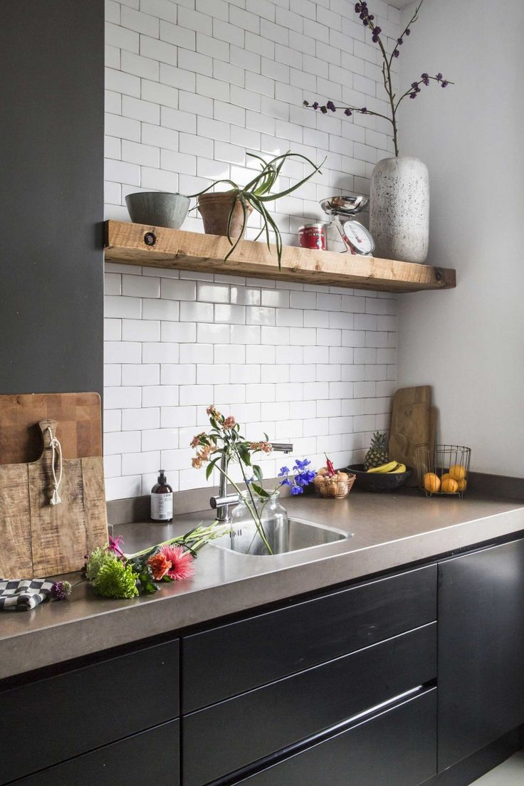 Black kitchen with natural stone and white tiles …