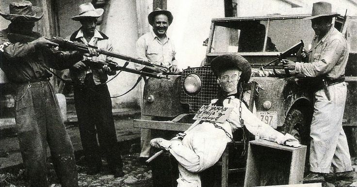 Rebels aim their guns at a doll portraying the Guatemalan president, Jacobo Árbenz, during the 1954 CIA backed coup d'etat.