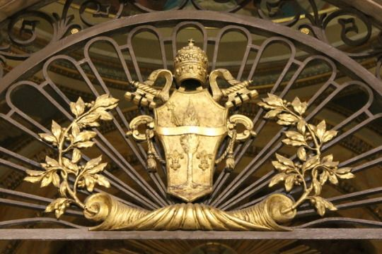 Coat of arms of Pope Leo XIII wrought in iron at the entrance to a side chapel in the Basilica of San Crisogono, Rome.
