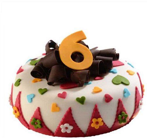 Dětský dort č. 21 Dětský dort obalovaný fondánem, dozdoben fondánovými vykrajovátky a hoblinkami z čokolády.