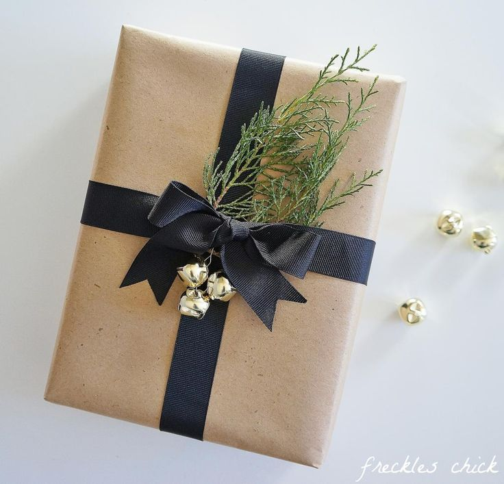 Holiday gift wrapping: kraft paper, jingle bells, black ribbon, & evergreen