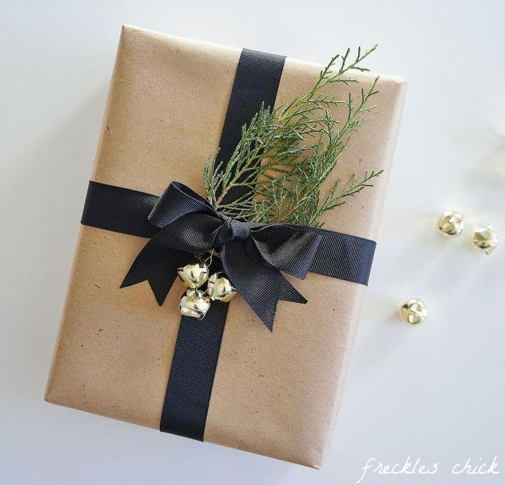 Holiday gift wrapping: kraft paper, jingle bells, black ribbon, & evergreen