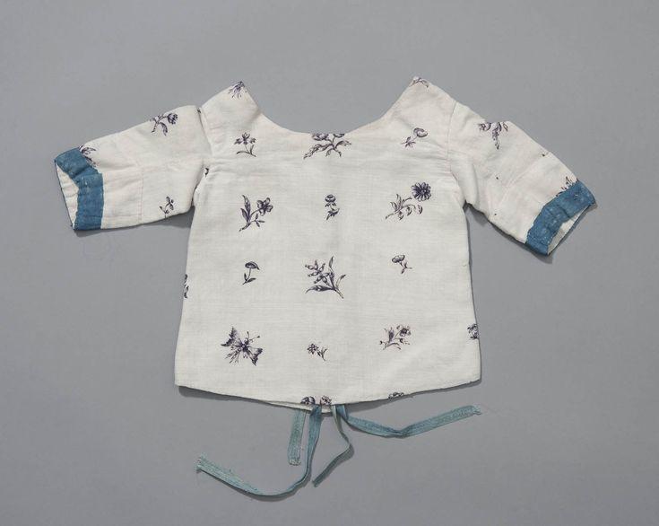 babyjakje, Groningen, 1800-1850 Babyjakje van bedrukte katoen met een paars strooimotiefje tegen een wit fond. Het jakje is afgewerkt met blauw lint. Deze kleurcombinatie kan duiden op het gebruik voor een kindje in de rouw. In later tijden waren paars en blauw vaak kleuren voor de lichte rouw. Of dit ook al zo was toen dit jakje werd gebruikt is niet duidelijk. #Groningen
