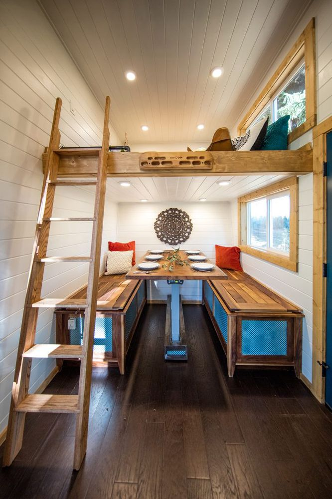 A large dining table seats six and a cozy office space is located in the loft area above.