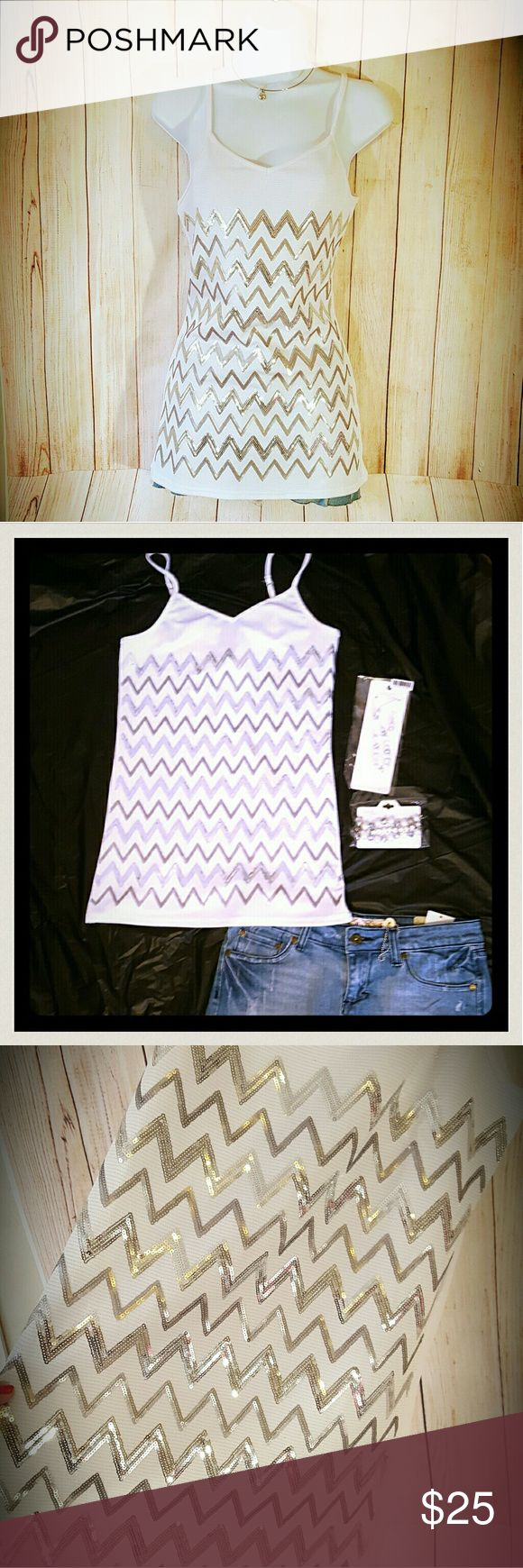 """White Tank Silver Chevron Sequins Shiny Stretchy Gorgeous white tank with shiny silver sequins. Brand: Vanity. Size medium (fitted but stretchy to fit most sizes). Adjustable shoulder straps to make it more conservative or more low cut. Still new with tags. Laying flat and unstretched, it measures 15.5"""" across the chest, 28"""" long.   Smoke free home. I will gladly bundle items to give you a discount (the more you buy, the cheaper I can let everything go!). Many items can be added on for only…"""