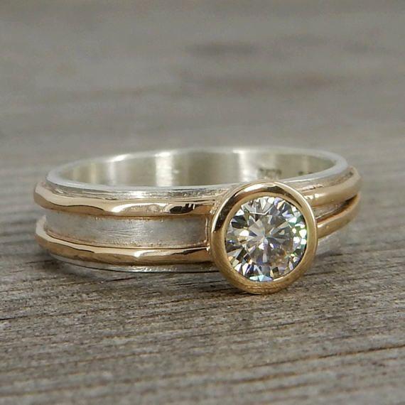 Eine wunderschöne 5mm (entspricht einer 0,5 Karat Diamant) Moissanite sitzt in einer 14 k gold Lünette auf einer 5mm breiten geschichtet 14 k gelb Gold und Silber Band. Dies ist ein Design, die wirklich gut als ein Ehering oder für jeden anderen Anlass arbeiten kann. Alle