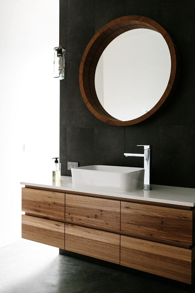 floating reclaimed wood vanity and black bathroom wall