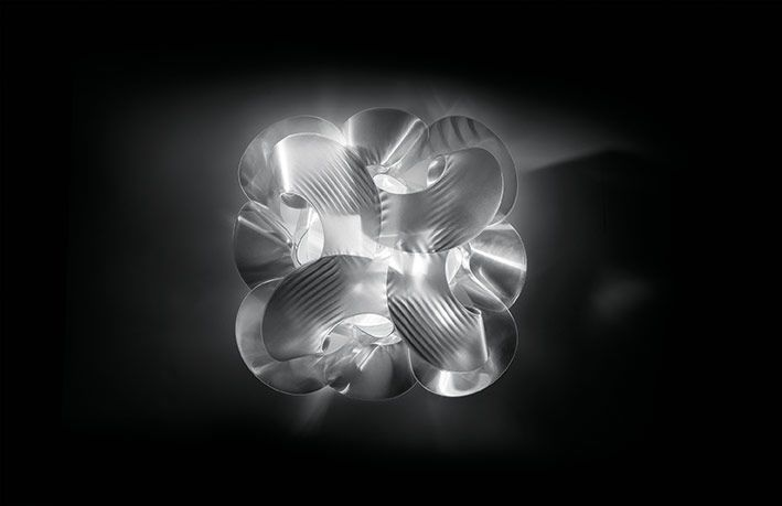 Fabula appears to be a long piece of fabric wound around itself. The new, iridescent versions for ceiling and wall are 60 cm in diameter, handmade with Lentiflex®, and feature 5 light sources, making them perfect for illuminating large spaces. The ceiling, wall, and 48 cm suspension bring a touch of elegance to any space. www.slamp.com