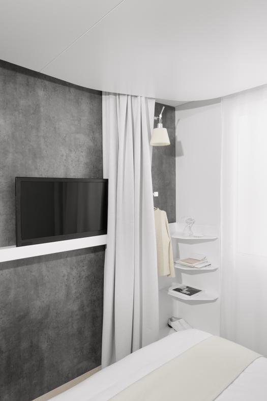 La tenda della stanza, oltre alla funzione di oscurare la finestra, si allunga anche ai piedi del letto, chiudendo l'angolo con gli scaffali a muro
