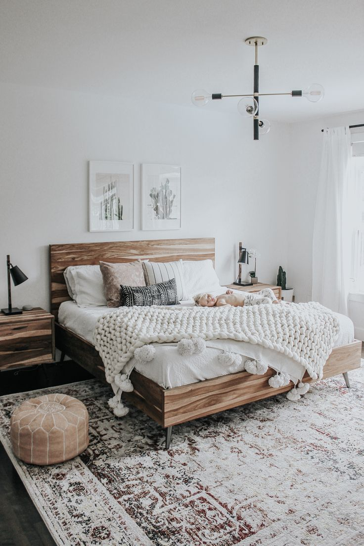 Neutral Bedroom Design With Extra Large Rug And Wood Bed