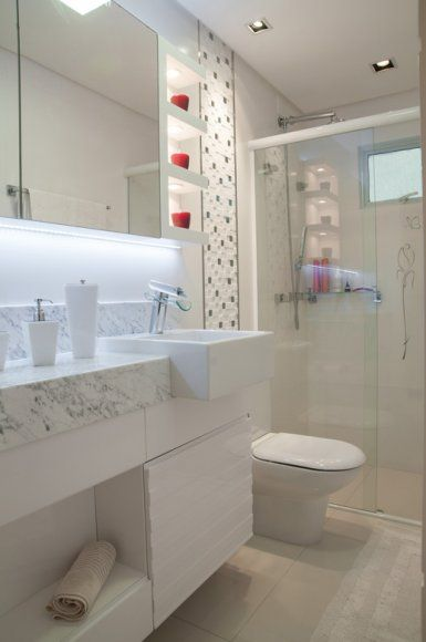 O banheiro social recebeu revestimentos retificados branco fosco para valorizar os azulejos com mosaicos de mármore branco com filetes de aço inox aplicados na lateral da bancada, em mármore carrara.