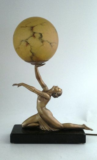 Art Deco table lamp in the form of a kneeling female holding aloft an original amber marbled crackle glass shade, on a black and bronze marble base. 50cm H. 35cm L. including the foot overhang and 12cm D. British circa 1930. (hva)