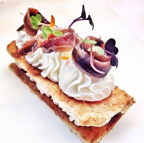 Milhojas de Torta de Aceite Sin Azúcar de Inés Rosales con crema de queso, anchoas y brotes de rábano morado.