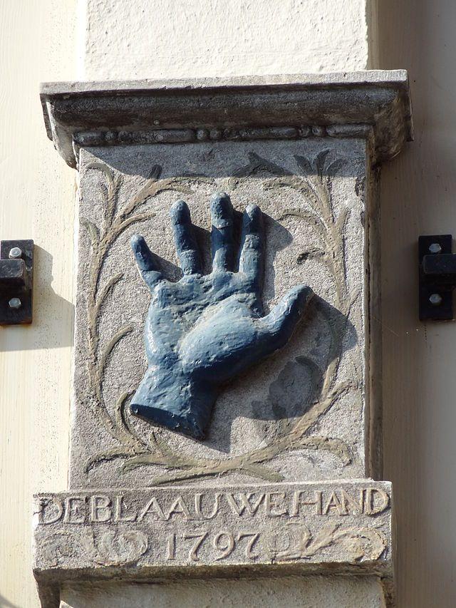 Tussen de twee vensters op de eerste verdieping van Achter de Hoofdwacht 3 is deze mooie gevelsteen uit 1797 te vinden. Het is al ruim twee eeuwen lang het herkenningsteken van het oudste café van de stad: In de Blaauwe Hand. Het café dankt zijn naam mogelijk aan het feit dat het regelmatig werd bezocht door wevers van de naastgelegen Lakenhal, die door het blauwsel vaak gekleurde handen hadden.