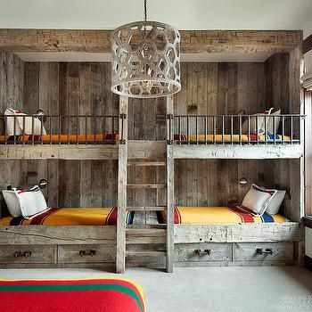 Rustic, cottage bedroom with lofted bunk beds for four, exposed wooden walls, drawers underneath for storage and a ladder | Orrick and Company