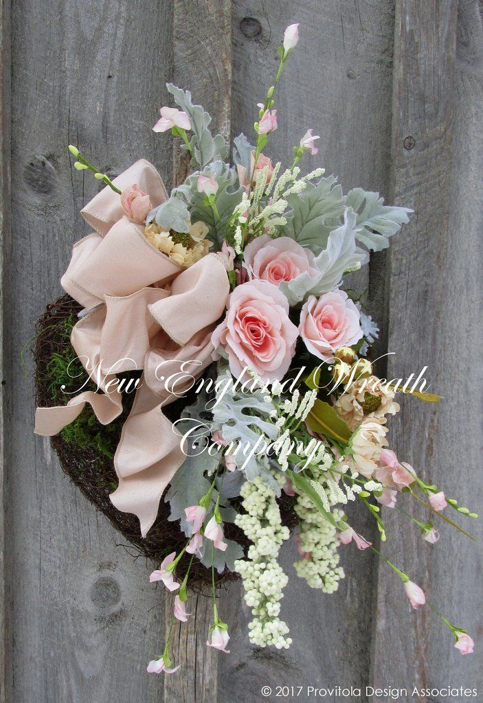 Elegant Moss Heart Wreath. Lovely and romantic, an elegant collection of Tea Roses and garden favorites in baby pink, blush and soft ivory mingle with meadow grass and lush flocked greenery, accented