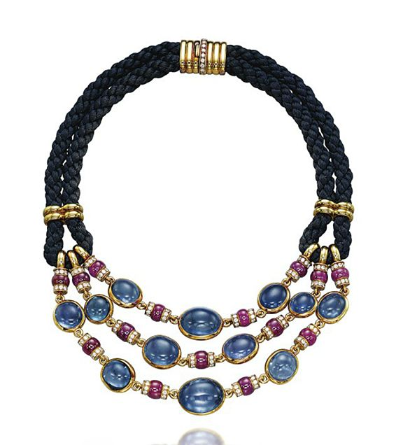 A SAPPHIRE, RUBY AND DIAMOND NECKLACE, BY BULGARI  Designed as three rows of spectacle-set cabochon sapphires linked by ruby bead and diamond-set rondelle spacers, to the double dark blue silk cord and gold clasp, 39.5 cm Signed and with maker's mark for Bulgari