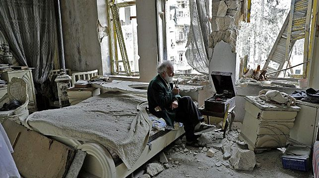 Among the many confronting viral images of Syria's bloody civil war the photograph of an elderly man sitting in his shelled out apartment stands out for being a haunting portrayal of the conflict.