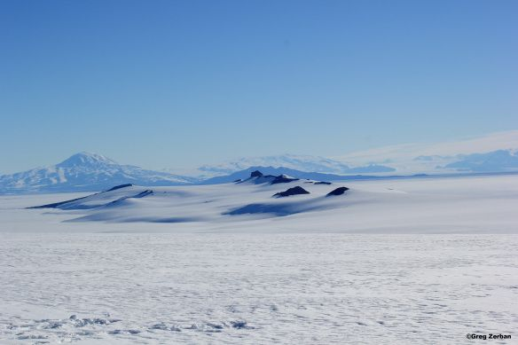 This picture is looking down the peninsula with Mt. Discovery in the left background.  The US Antarctic base McMurdo Station, and the New Zealand Scott Base are located at the end of the peninsula.   On the left side of the peninsula is the Ross Ice Shelf, and on the right side is the Ross Sea.  This is one of the most southern areas accessible by ship which is why Robert Falcon Scott chose this location for his Discovery Hut.