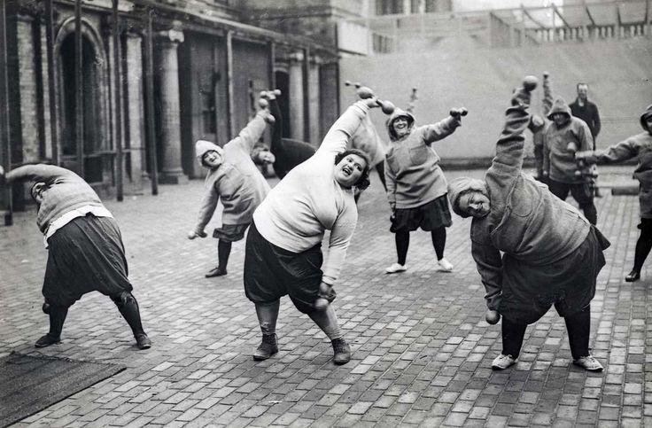 Gymnastiek, afvallen. Groep dikke vrouwen ondergaat afslankcursus op een binnenplaats te New York. Datum onbekend.