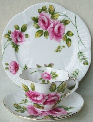 ...Looks like Shelley style cup. Lovely pink twosome roses on white, like the detail on rim of lunchplate