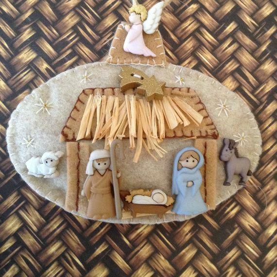 Adorno navideño hecho con fieltro y rafia, y los botones Nativity de Dress-It-Up. Representa un portal de belén con el ángel en la parte superior.