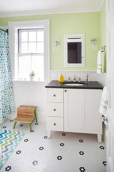 The vanity and tile floor of the children's bath feature a classic black-and-white theme, allowing the room's style to evolve as the kids grow. For now, the cheery room includes vivid accents of green, blue, and violet.