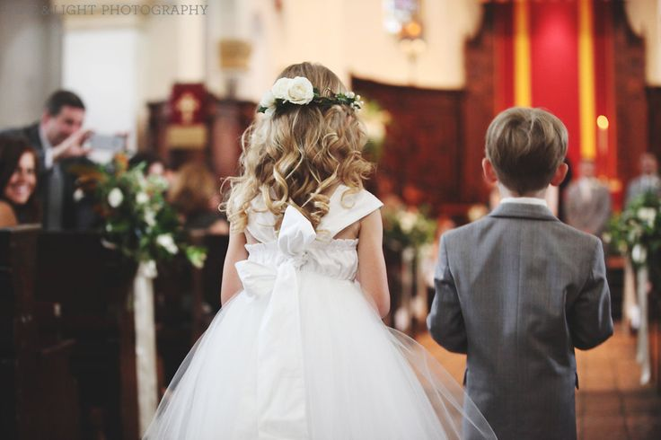the flower girl heads down the chapel aisle wearing her flower crown of bacopa and white spray roses.