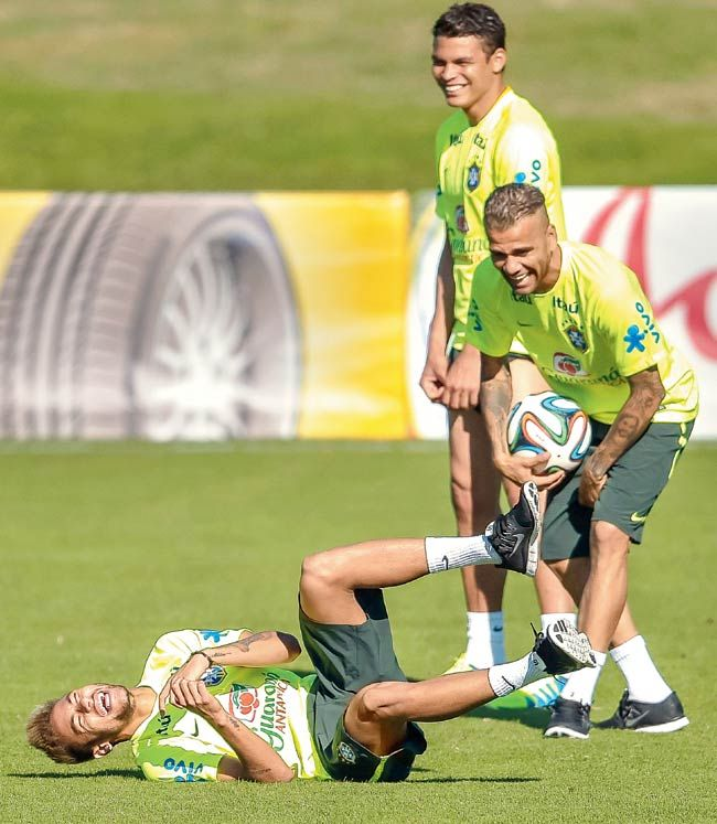 Neymar (left) jokes with Daniel Alves and Thiago Silva (back) during a training session