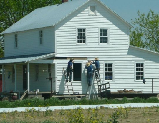 Amish men doing the final finishing work on a house in ethridge, TN, that they built from the ground up.