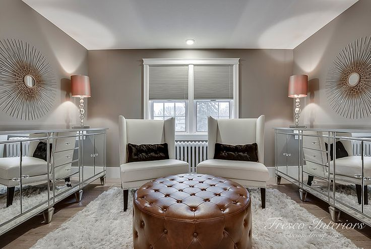 Elegant Master lounge.  Boutique style decor and cozy, luxurious design. Master bedrooms are meant to be lavish!  The mirrored dressers create the illusion of a larger space, while the rich tufted ottoman and white wing back chairs offer an intimate place to relax and unwind.