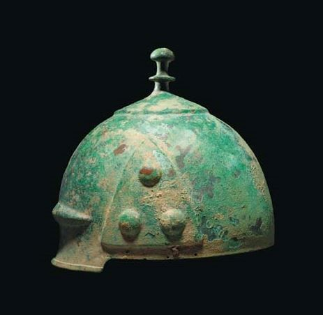 Celtic helmet, 3th-2nd century B.C. Of domed form with attached tall knopped finial, moulded inverted-V ribs above the brow extending into encircling band around the crown, each side with three raised decorative bosses, with dents, 25 cm high. Private collection, from Christie's auction