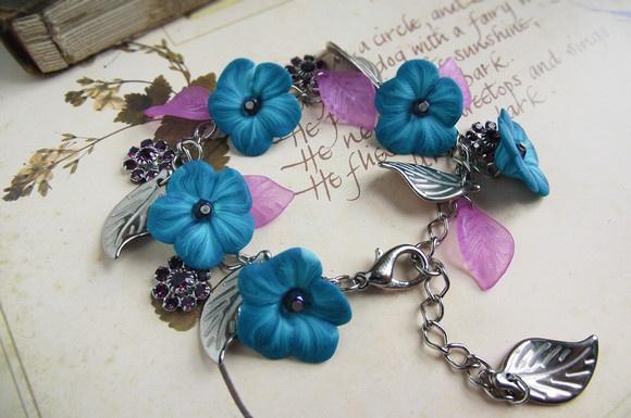 Linda e única pulseira de flores azuis, entremeadas por pingentes de folhas lilases e prateadas, e pingentes de cristaizinhos roxos em forma de flor. As flores foram feitas à mão, de cerâmica plástica, portanto cada uma é diferente da outra. No centro de cada uma, há um pequeno cristal lilás.  Comprimento: 17 cm, mais 4 cm de extensor, total de 21 cm.