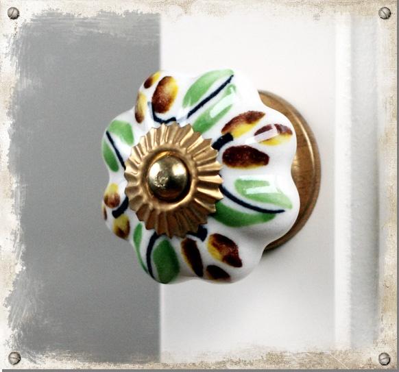 Vit knopp i porslin med gröna och bruna blad #knoppar #knobs