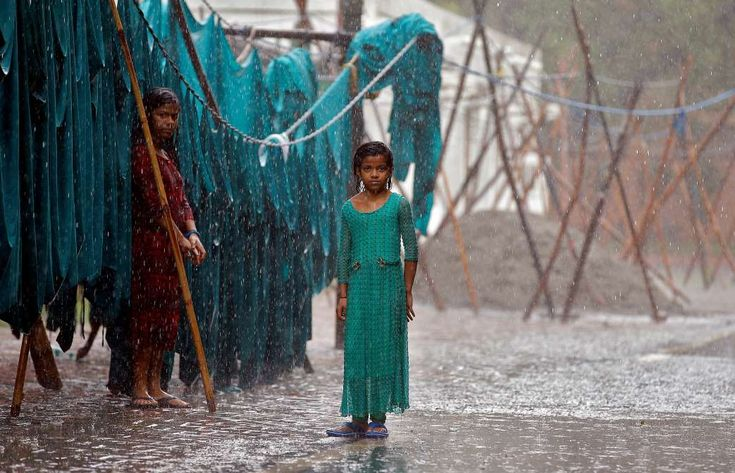Girls stand in monsoon rains beside an open laundry in New Delhi, India, June 21, 2017. - Cathal McNaughton/Reuters