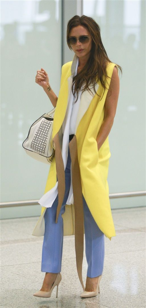Victoria Beckham. Love the yellow street fashion sleeveless jacket. Long jackets never go out they make a huge statement.