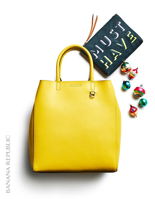 "Gift idea she'll love: a bold carryall tote made from genuine leather paired with a playful conversation clutch. This yellow handbag's large size makes it ideal for carrying from desk to dinner and its bold yellow hue is sure to make a statement. Add in the small zip pouch that reads ""must have"" for a playful, yet practical addition to this gift (read: she can tuck this in her tote, or carry it on its own aka double duty)."