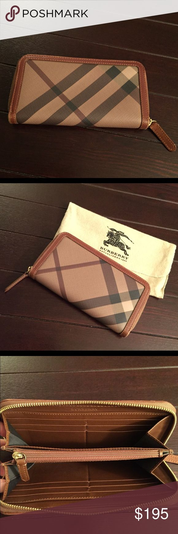 """BURBERRY Smoked Check Zip Around Wallet Brown BURBERRY Smoked Check Zip Around Wallet Brown  * Brand: Burberry * Style: Smoked Check Zip Wallet * Color: Chocolate/Black/Tan * Measurements: 7.5"""" x 4"""" x 1"""" * Material: PVC/ Leather Trim * Features: 12 credit card slots, 2 open compartments, zippered center pocket, 2 bills sleeves * Very good pre-owned condition with signs of normal use on edges of wallet; carried for about a year and stored in storage bag Burberry Bags Wallets"""