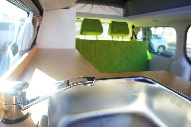 Hyundai campervan conversion with white ply cabinetry, timber bench top and grass green upholstery.