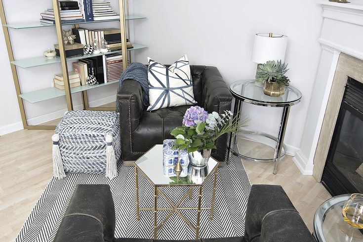 beautiful modern and traditional eclectic fireplace are with leather button tufted swivel chairs, blue, black and white accents and a chunky fireplace surround