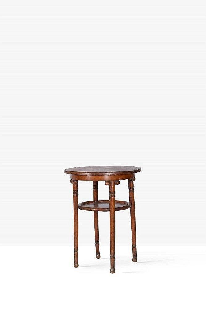JOSEF HOFFMANN (1870-1956) <br>ATTRIBUÉ À POUR KOHN <br>Guéridon en hêtre teinté noyer à deux plateaux ronds et quatre <br>pieds cylindriques ornés de boules sous la ceinture. <br>Etiquette de Kohn. <br>Variante du modèle n°923/70 du catalogue. <br>H. : 77 cm. D. : 60 cm.